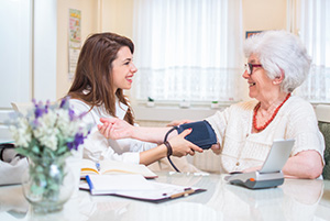 home health care home health aide female with an elderly patient.