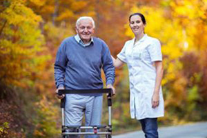 woman wearing a white doctors coat with an elderly male wearing a blue sweater and using a walker.