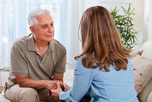 Las vegas home health care speech therapy woman with brunette hair with her back towards us wearing a blue shirt speaking with an elderly caucasian male.