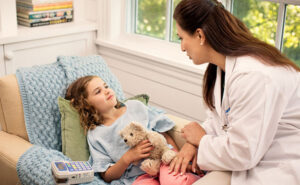 Home Health Care for Children, a nurse wearing a white nurse coat tending to a child in the comfort of her own home.